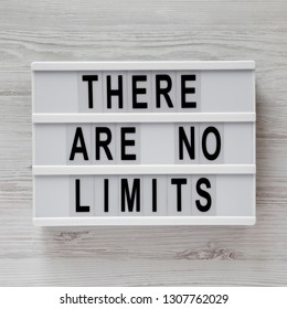 Modern box with text 'There are no limits' on a white wooden background, top view. Flat lay, overhead.
