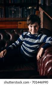 Modern boy in elegant clothes sitting on a sofa in luxurious apartments. School fashion.