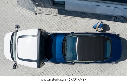 Modern Brand New Convertible Car on Towing Truck Delivered to Client Home. Aerial View. Transportation and Car Sales Theme.