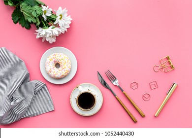 modern breakfast desing with sweet donut, coffee and flowers on woman pink desk background top view mock up
