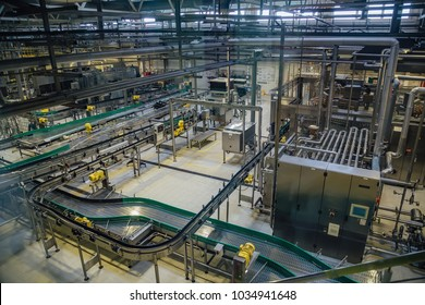 Modern brewery production line, aerial view. Conveyor belt, pipeline for ingredient delivery, machinery, tools, vats, no people.