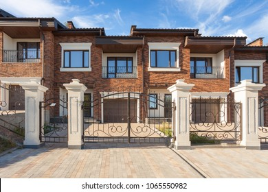Modern brick house with plastic windows,  modern wrought-iron gates and chimney