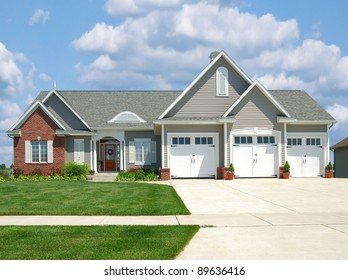 Modern brick and vinyl siding house in the suburbs with a three car garage in summer.