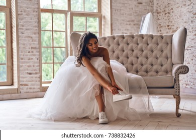 Modern bride. Attractive young woman in wedding dress putting on sports shoes and smiling while sitting on the sofa
