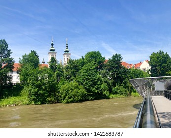 Modern bridge over river Murr and beautiful old church towers in Graz old town, Austria