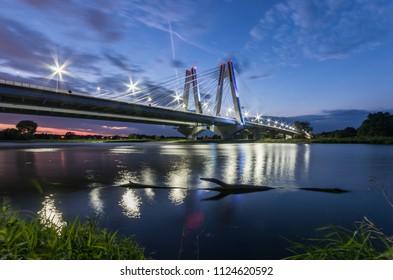 modern bridge over Vistula river, Krakow, Poland, illuminated in the night