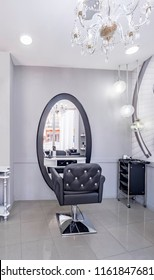 Modern bright beauty salon or baber shop. Hair salon interior business with black and white luxury decor. Detail of the chair and mirror