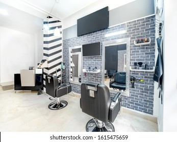 Modern bright beauty salon. Hair salon interior business with industrial minimal look. Black and white decoration with mirrors, chairs,tv screen and mockup banners