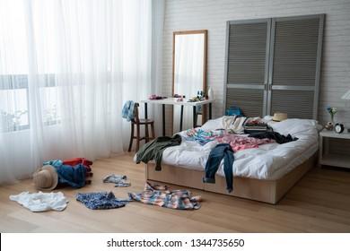 白いベッドと床に散らばる汚い服を着た、現代的な明るい寝室。居心地の良いアパートに誰もいない空室夏休みと春休みのコンセプトライフスタイルの荷物を詰め込む。