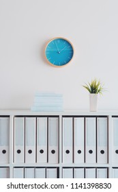 Modern bright business office interior detail depicting wall clock and shelf with books, plant and file ring binders