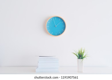 Modern bright business office interior detail depicting wall clock and shelf with books and plant