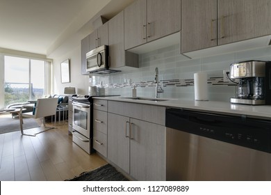 Modern, bright, clean, kitchen with stainless steel appliances with a living room. Interior design.