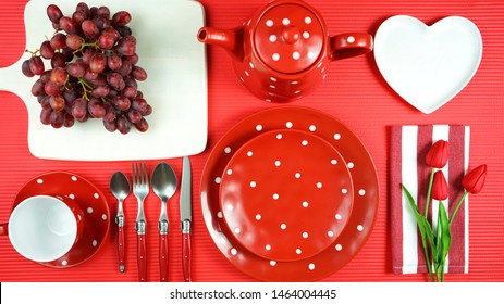 Modern bright colorful red theme morning breakfast or brunch table setting, flat lay.