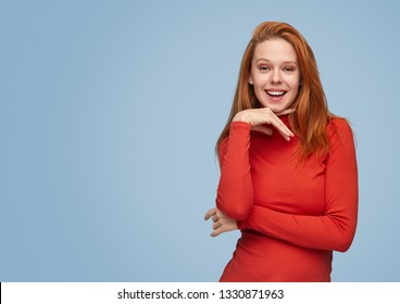 Modern bright ginger girl in red shirt standing in flirty pose on blue background looking at camera