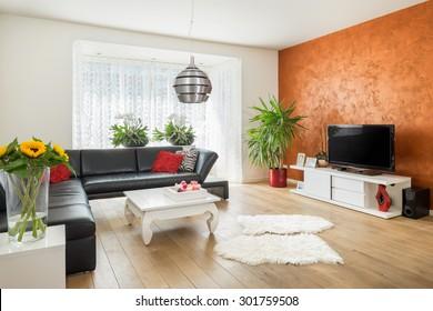 Modernes, helles Interieur mit Holzboden und orangefarbener Wand im europäischen Haus