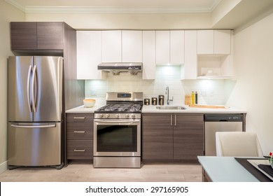 Modern bright kitchen with stainless steel appliances and dinner table. Interior design.
