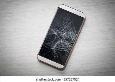 Modern broken mobile phone on wooden background.