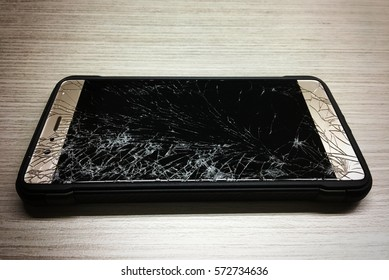 Modern broken mobile smart phone damaged by accident on wooden table