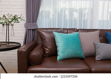 modern brown sofa and many blue pillows in spacious livingroom.
