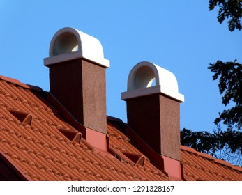 modern brown stucco finished chimneys with white ceramic cap stone, bright brown red clay tile roof tiles & clay vents under clear blue sky on crisp winter day with pine branch. construction concept.