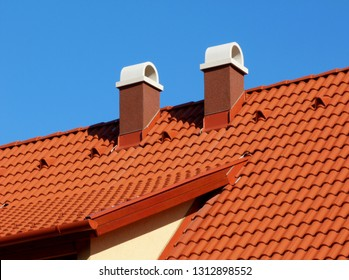 modern brown stucco finished chimneys with white ceramic cap stone, bright brown red clay tile roof tiles & clay vents under clear blue sky on crisp winter day in bright sunlight. construction concept