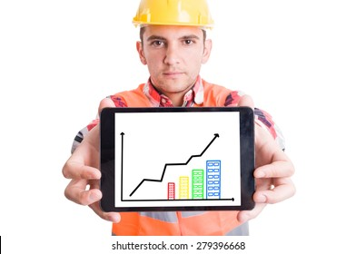 Modern builder holding tablet with growing financial charts or graph