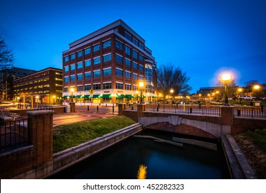 Modern building and bridge over Carroll Creek at night, at Carroll Creek Linear Park, in Frederick, Maryland.