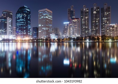 modern building bright in night city with skyline symmetric water mirror reflection. night cityscape concept.
