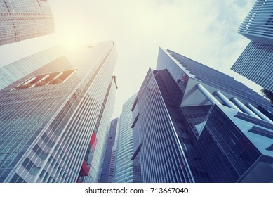 Modern building at business center city. Look up view with sunlight. Architecture, construction, investment, finance. Abstract background.
