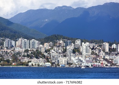 Modern building skyline of West Vancouver district surrounded by mountains (Vancouver, British Columbia).