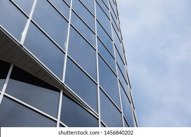 Modern building with tinted windows against sky, low angle view. Urban architecture