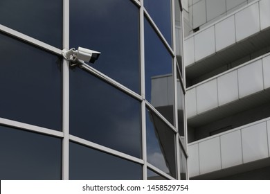 Modern building with tinted windows and CCTV camera, low angle view. Urban architecture