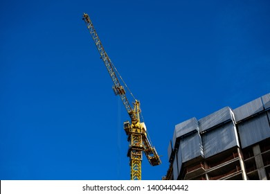 Modern building under construction with crane From below of constructing building with high crane under clear sky