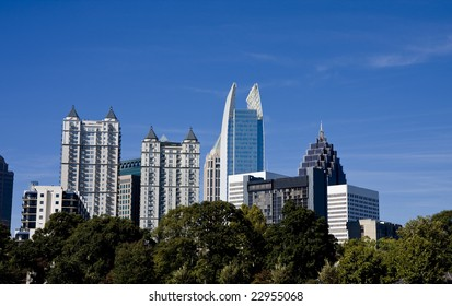 Modern buildings of a city skylines past the trees in a park
