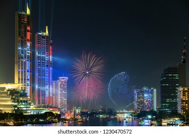 Modern buildings in the city with water reflection, firework, light show at night time.