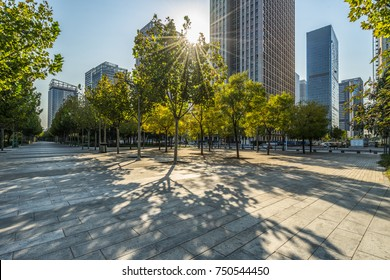 modern buildings and empty pavement under sunbeam