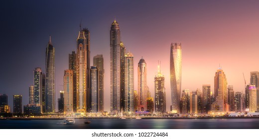 Modern buildings with gold reflection of Dubai Marina bay view from Palm Jumeirah at sunset, UAE