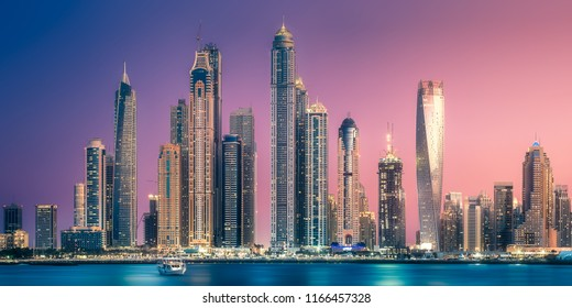 Modern buildings with gold reflection of sunset on Dubai Marina bay view from Palm Jumeirah, UAE.