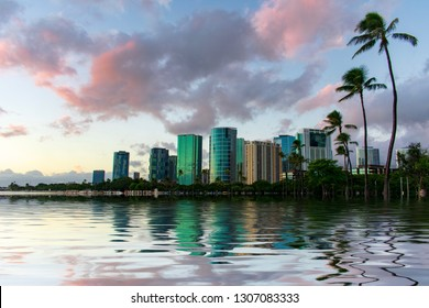 Modern buildings in Honolulu, Hawaii at evening with their reflection into the water