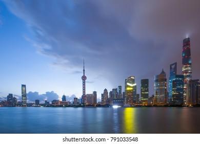 modern buildings near river in shanghai lvjiazui CBD in cloud sky at twilight