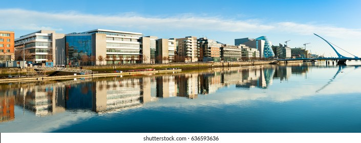 Modern buildings and offices on Liffey river in Dublin on a bright sunny day, bridge on the right is a famous Harp bridge. Panoramic image.