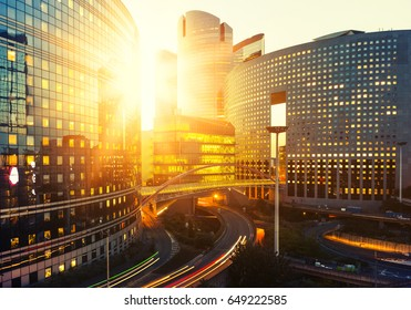 Modern buildings in Paris business district La Defense. Glass facade skyscrapers on a bright sunny day with sunbeams in the blue sky. Economy, finances, business activity and city traffic concept