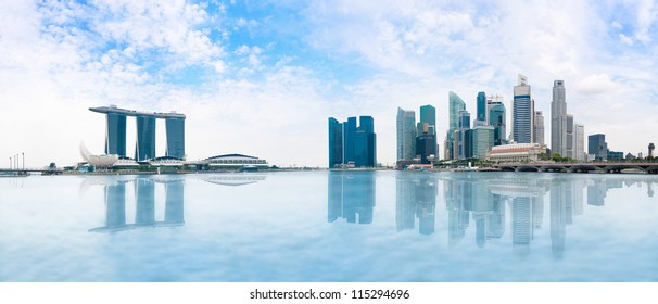 Modern buildings of Singapore skyline landscape in business district  with blue sky and reflection in water of Marina Bay