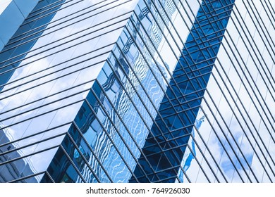 Modern business architecture, abstract fragment, walls made of glass and steel with reflections of blue sky