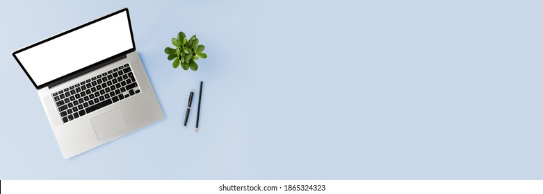 Modern business background with laptop with empty screen and accessories on blue table. Office desktop. Top view. Banner
