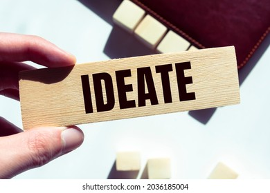 Modern business buzzword - ideate. Word on wooden blocks on a brown background. Close up.