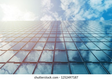 modern business high rise glass building and blue sky with clouds and sun