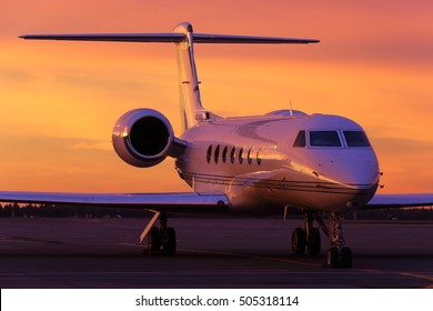 Modern business jet standing on a parking position during sunrise.