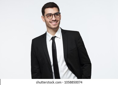 Modern business man in black suit looking away while standing in studio, isolated on grey background
