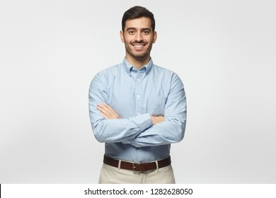 Modern business man in casual blue shirt standing with crossed arms, isolated on gray background